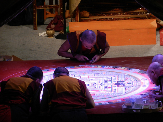 Tibetan Buddhist artist monks completing the lettering around the Kalachakra mandala, one fills in the white edge, others wear masks, plastic cups of colored sand, on stage, Kalachakra for World Peace, Washington D.C., USA